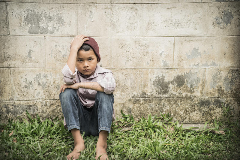 Scared and alone. Young asian boy suffering physical abuse, he also mentally and emotionally abused and is at high risk of being trafficked royalty free stock image