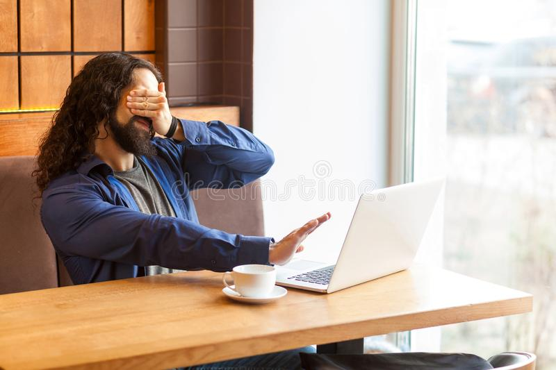 Scared bearded young man freelancer in casual style and long curly hair sitting and talking with his friend in laptop, covering royalty free stock photos