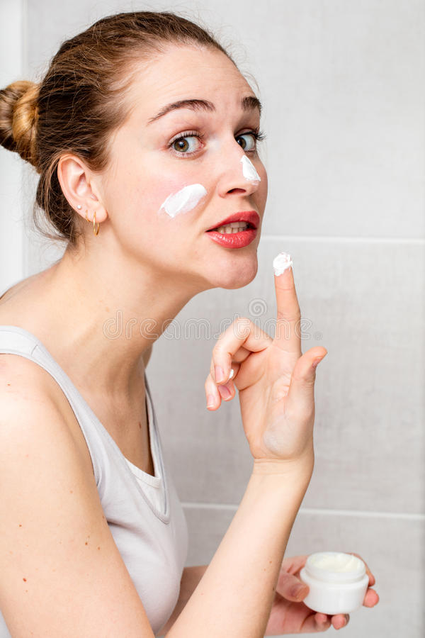 Scared beautiful girl applying dangerous face cream for risky routine stock image