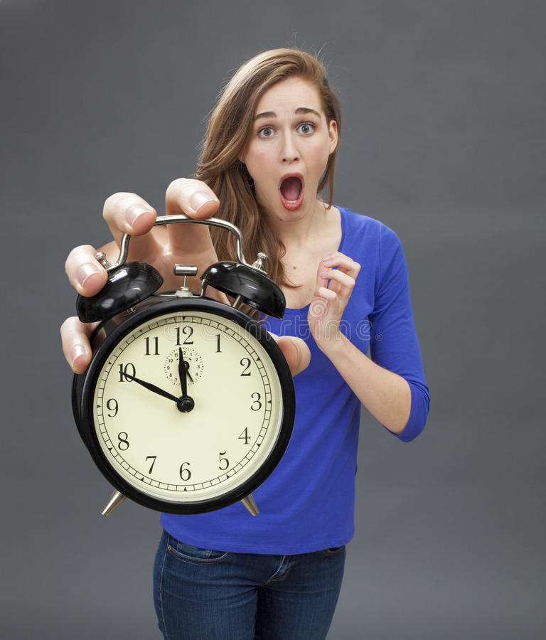 Scared beautiful young woman standing with a clock for stressful deadlines royalty free stock photos