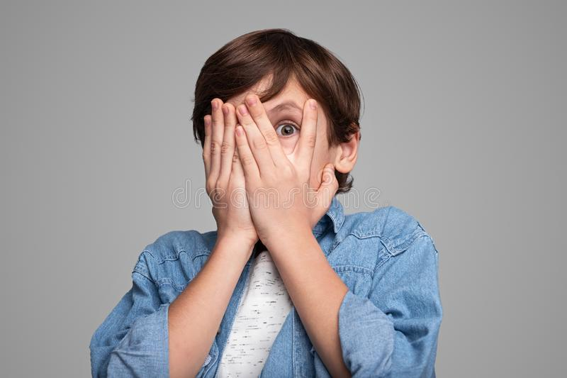 Scared boy covering face. Terrified boy in casual outfit covering face with both hands and looking at camera through fingers while standing against gray stock photo