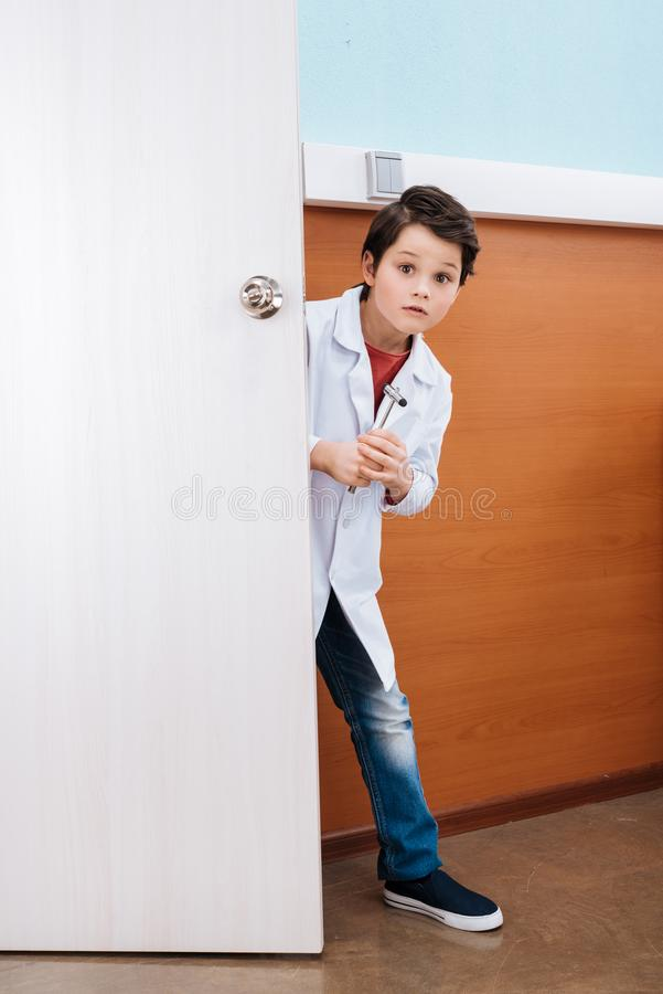 Smiling boy doctor with reflex hammer standing in doorway and looking royalty free stock images