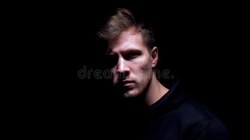 Scared bruised man standing against dark background, victim of hooligan, closeup stock photos