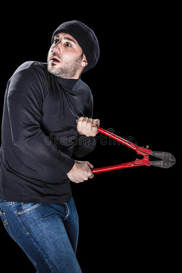 Scared burglar. A burglar wearing black clothes holding huge wire cutters over black background royalty free stock photos
