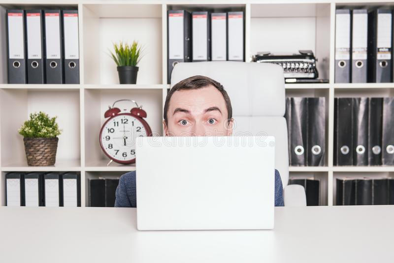 Scared business man hiding behind laptop royalty free stock photography