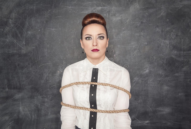Scared business woman tied with rope. On the blackboard background royalty free stock photo
