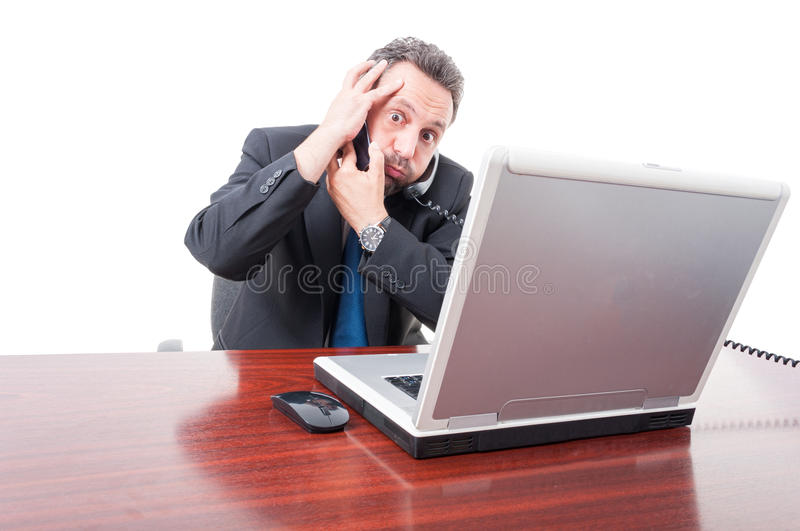 Scared businessman having trouble at work. Calling somebody to solve it on white studio background stock image