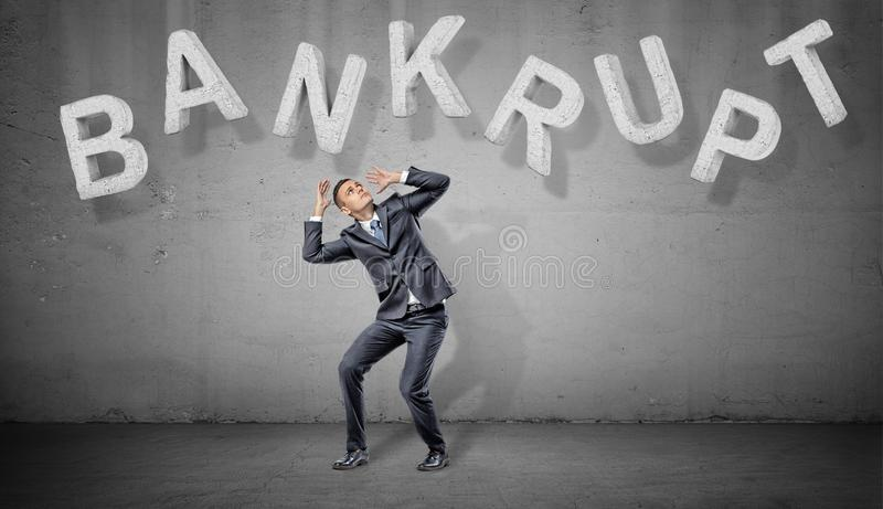 A scared businessman hides under large concrete letters making a word Bankrupt above him on a grey background. royalty free stock photo