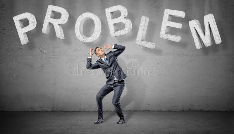 A scared businessman hides under large concrete letters making a word PROBLEM above him. royalty free stock image