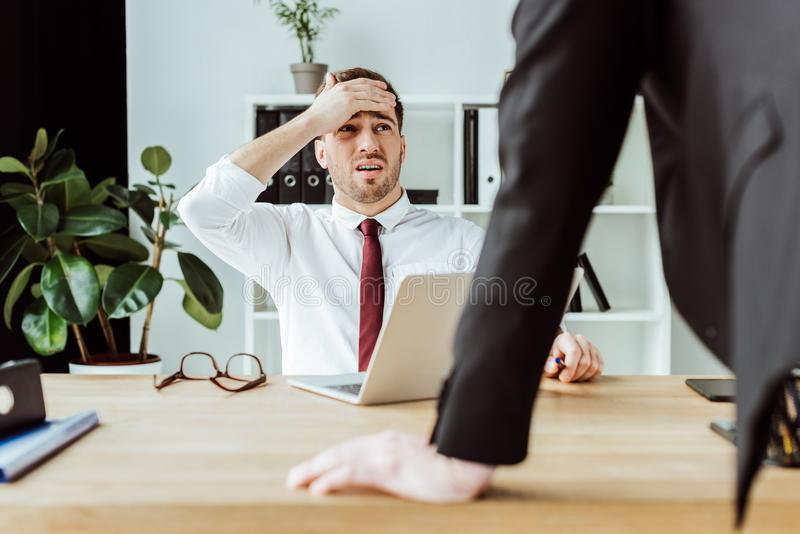 scared businessman with laptop looking at angry boss royalty free stock image