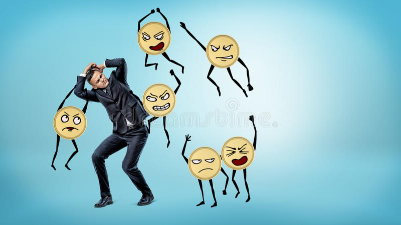 A scared businessman standing and hiding his face and body from many humanoid golden coins beating him. royalty free stock photography