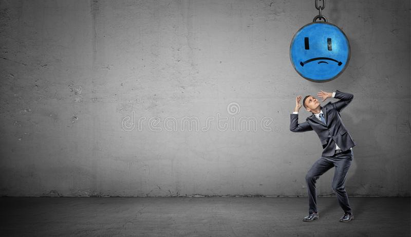 A scared businessman stands on concrete background under a wrecking ball with a painted blue sad face. royalty free stock photo