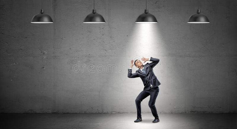 A scared businessman stands cowering under the rays of industrial pendant lights right above him. royalty free stock photos