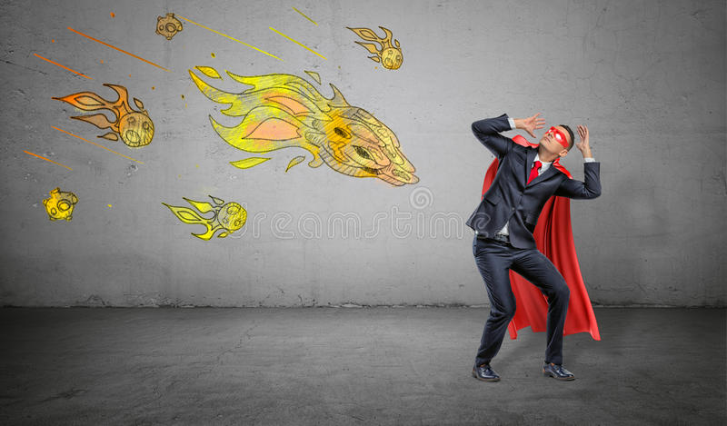 A scared businessman in a superhero cape cowering under an attack of yellow paper comets on concrete background. Business and competitors. Crisis management royalty free stock photo