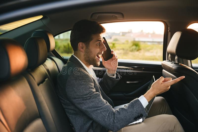 Scared businessman talking on mobile phone stock photo