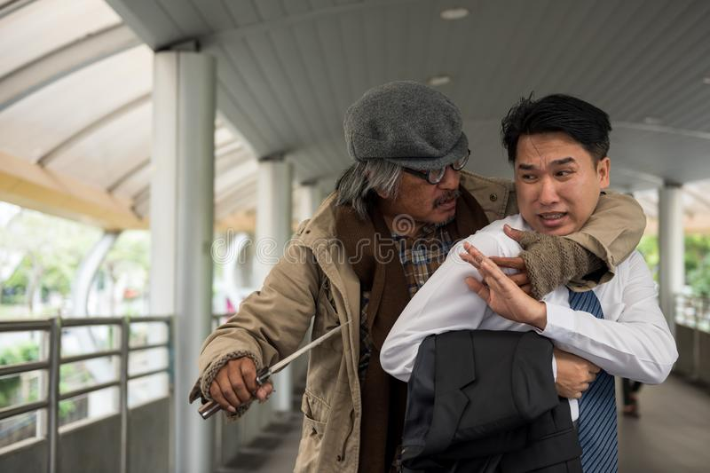 Scared Businessman threaten by knife stock photography