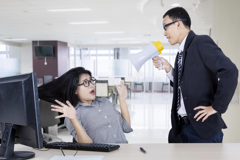 Scared businesswoman being shouted by her boss royalty free stock image