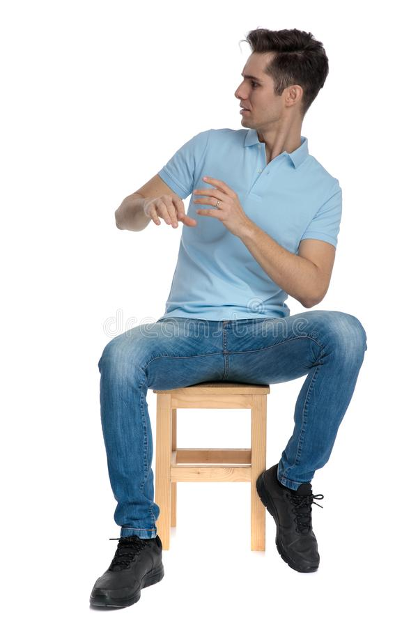 Scared casual guy looking to the side frightened. While wearing a blue shirt and jeans, sitting on a chair on white studio background royalty free stock photo