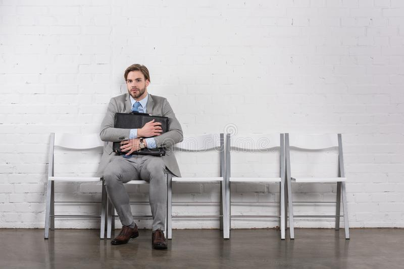 scared caucasian businessman with suitcase waiting stock images
