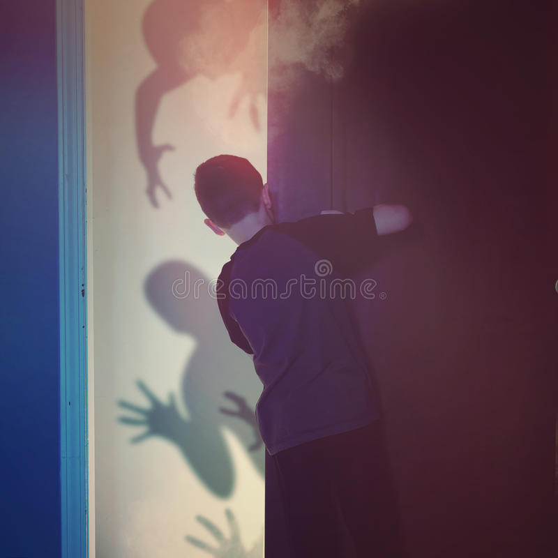 Scared Child Looking at Shadow Ghosts. A scared child is looking inside of a closet bedroom at black evil monster ghosts in the background for imagination or royalty free stock photo