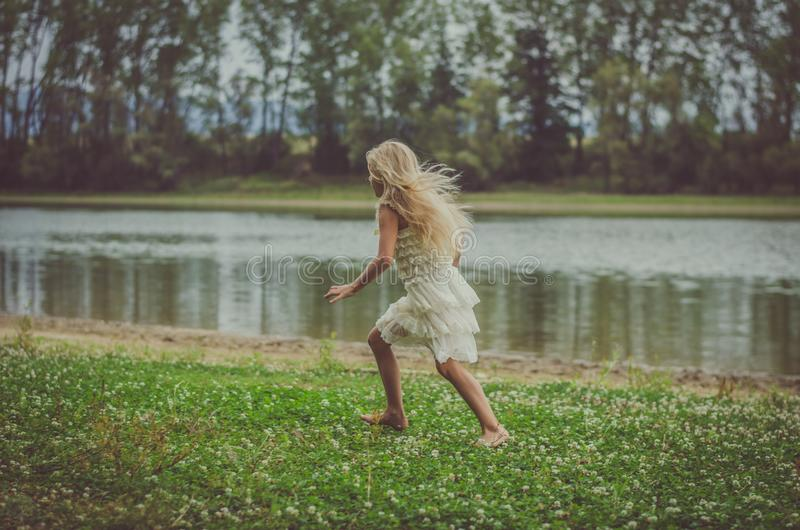 Scared child running away in the nature at dark atmosphere. Little child running away back view, in the nature by the river royalty free stock photos