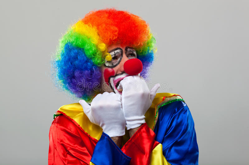 Scared clown over grey background. Scared clown portrait on grey background royalty free stock photography