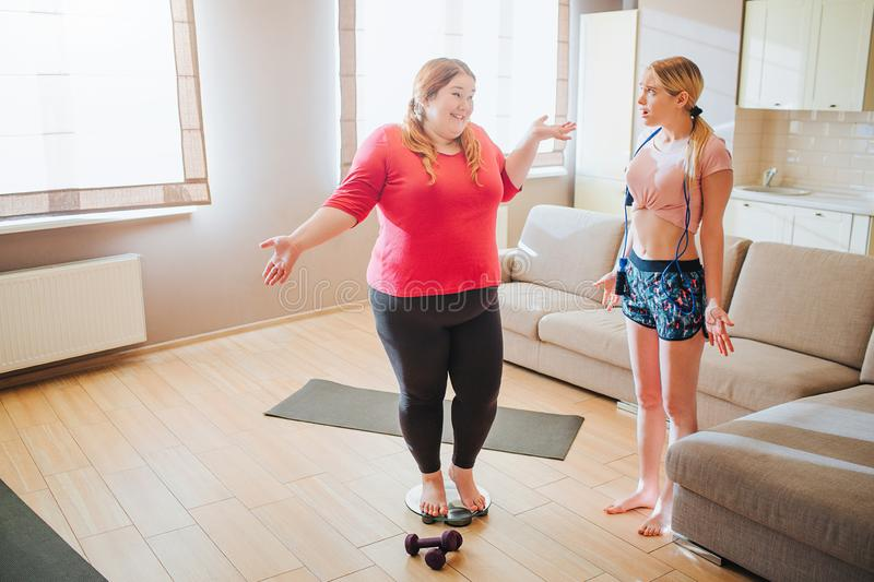 Scared confused young slim model look at plus size woman. Overweight girl stand on weight scale and smile. Jumping rope stock photo