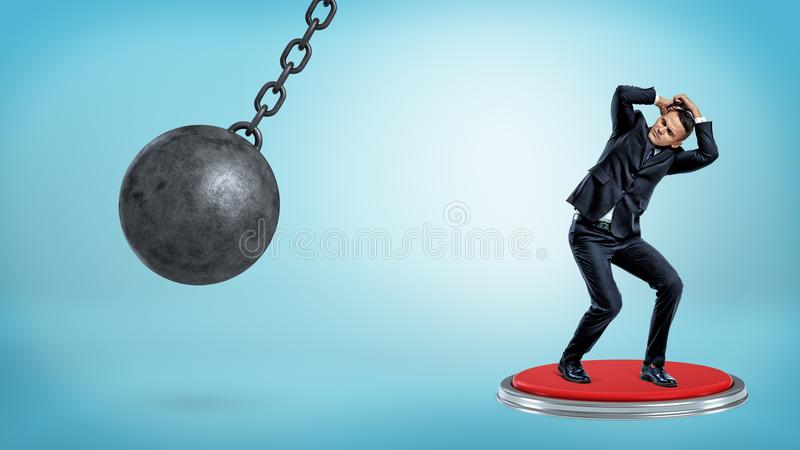 A scared cowering businessman stands on a huge push button and hides his head from a wrecking ball. royalty free stock photos