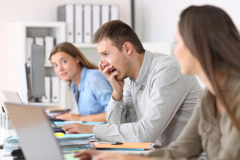 Scared employee after a big mistake on line. Side view portrait of a scared employee after a big mistake on line at office royalty free stock photography