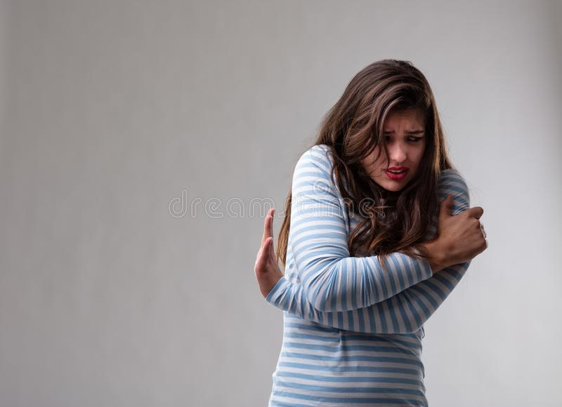Scared fearful young woman hugging herself stock photo