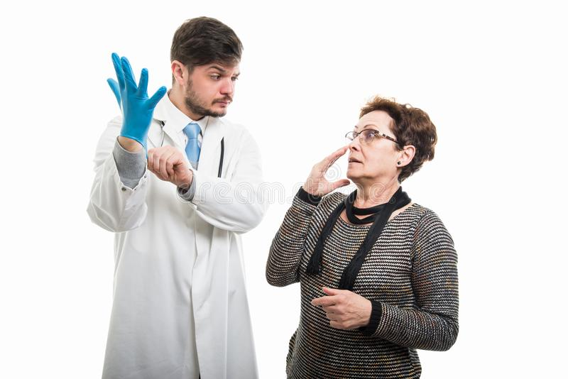 Scared female patient looking to suspicious male doctor with glove royalty free stock images