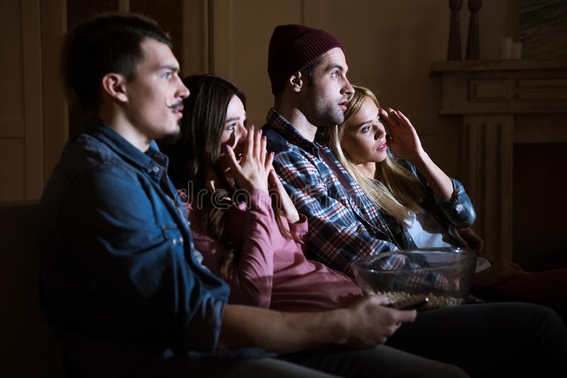 Scared friends watching movie with popcorn at home. Side view of scared friends watching movie with popcorn at home stock photo