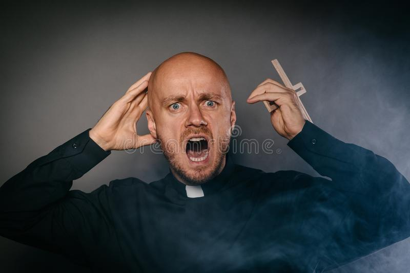Scared frightened catholic priest in black shir royalty free stock images