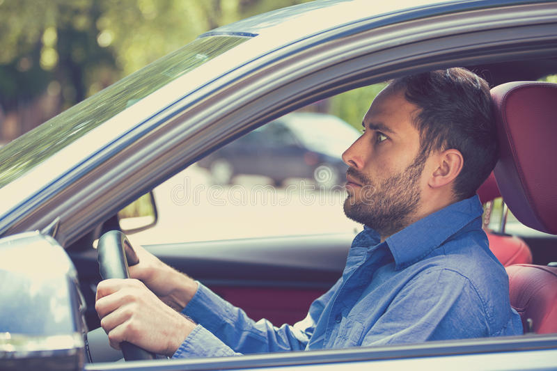 Scared funny looking young man driver in the car. Inexperienced anxious motorist. Scared funny looking young man driver in the car. Human emotion face expression royalty free stock image
