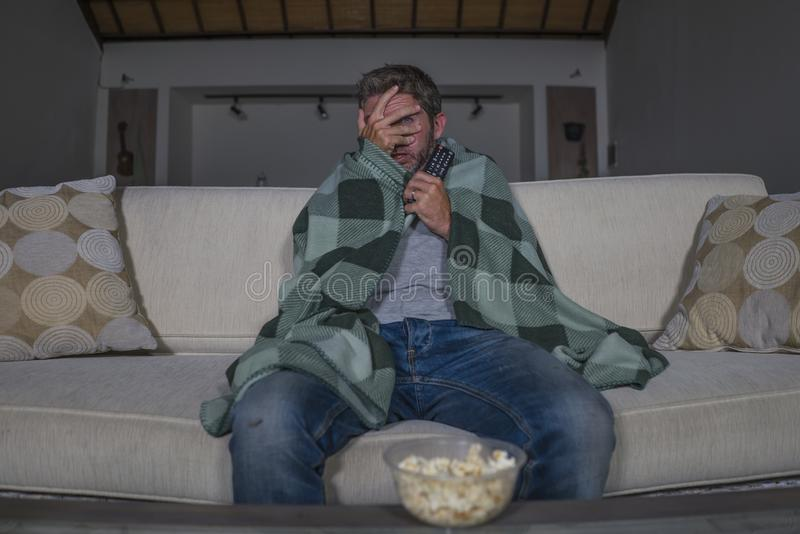 Scared and funny man alone at night in living room couch watching horror scary movie or scary show in television eating popcorn. Funny home lifestyle portrait of stock images