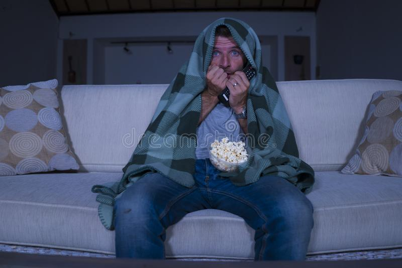Scared and funny man alone at night in living room couch watching horror scary movie or scary show in television eating popcorn. Funny home lifestyle portrait of royalty free stock photos