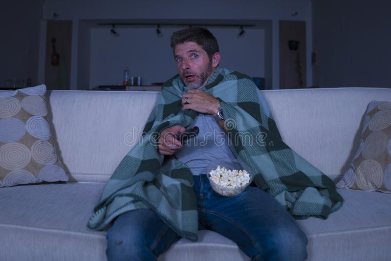 Scared and funny man alone at night in living room couch watching horror scary movie or scary show in television eating popcorn. Funny home lifestyle portrait of royalty free stock photo