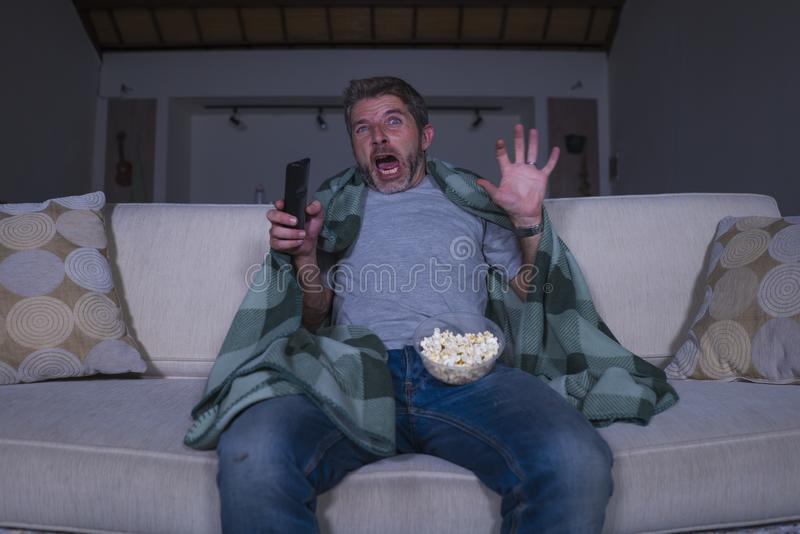Scared and funny man alone at night in living room couch watching horror scary movie in television screaming and eating popcorn. Funny home lifestyle portrait of royalty free stock photos