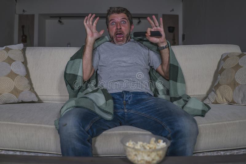 Scared and funny man alone at night in living room couch watching horror scary movie in television screaming and eating popcorn. Funny home lifestyle portrait of royalty free stock photo
