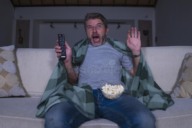 Scared and funny man alone at night in living room couch watching horror scary movie in television screaming and eating popcorn. Funny home lifestyle portrait of stock photo