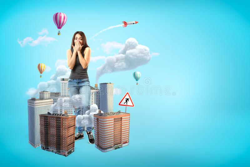 Scared giant young woman covering mouth with hands, standing amid high-rise buildings that are emitting smoke on blue. Background with copy space. Emergency stock photos