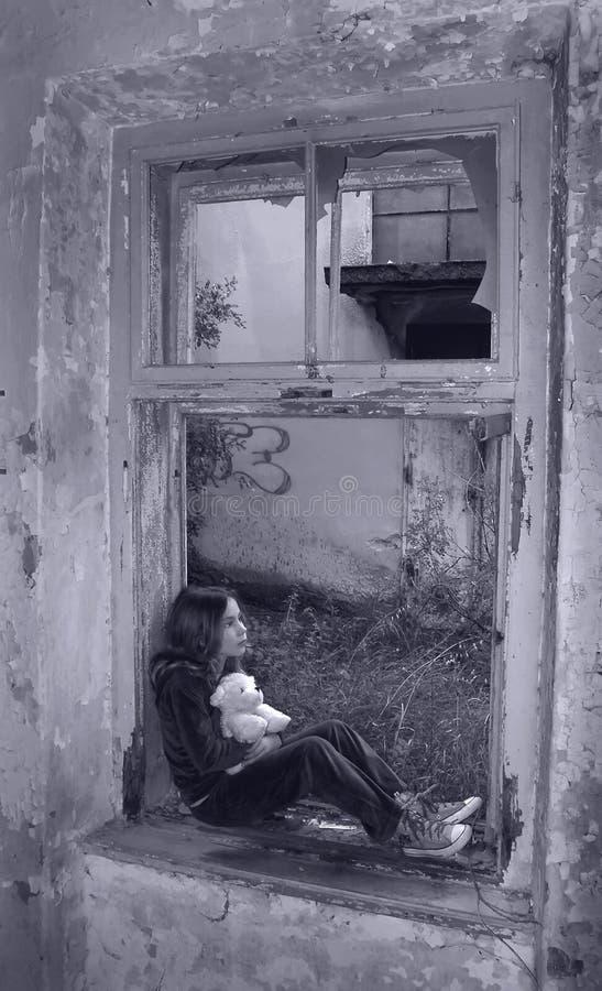 Scared girl on broken window stock image