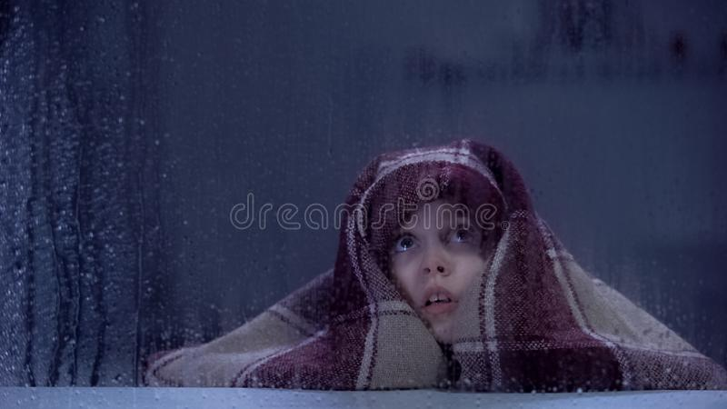 Scared girl covered in blanket frightened of ghost, fears and phobias concept stock image