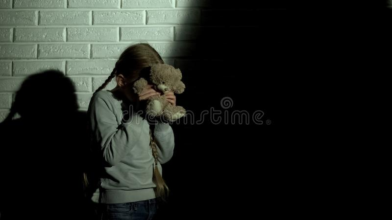 Scared girl covering eyes with teddy bear, ghost shadow on wall, nightmare royalty free stock photography