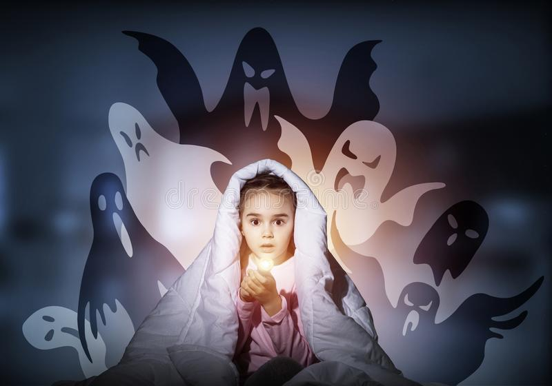 Scared girl with flashlight under blanket. Scared girl with flashlight hiding under blanket from imaginary phantoms. Frightened kid sitting in bed on night sky stock image