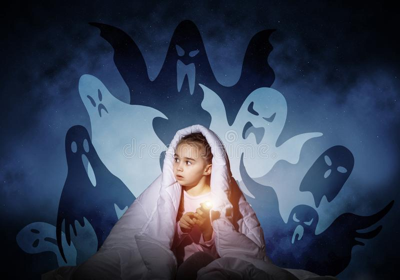 Scared girl with flashlight under blanket. Scared girl with flashlight hiding under blanket from imaginary phantoms. Frightened kid sitting in bed on night sky royalty free stock photo