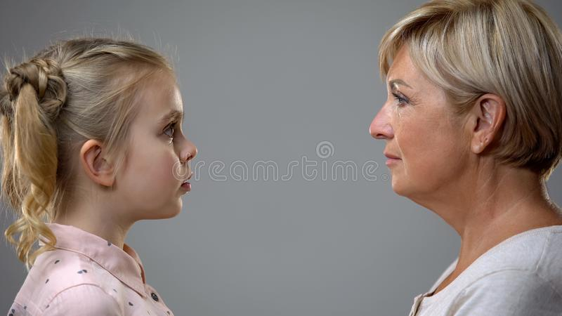 Scared girl looking at strict grandmother, difficult childhood, generation gap stock photography