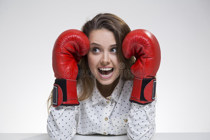 Scared girl in polka shirt wearing boxing gloves royalty free stock photo