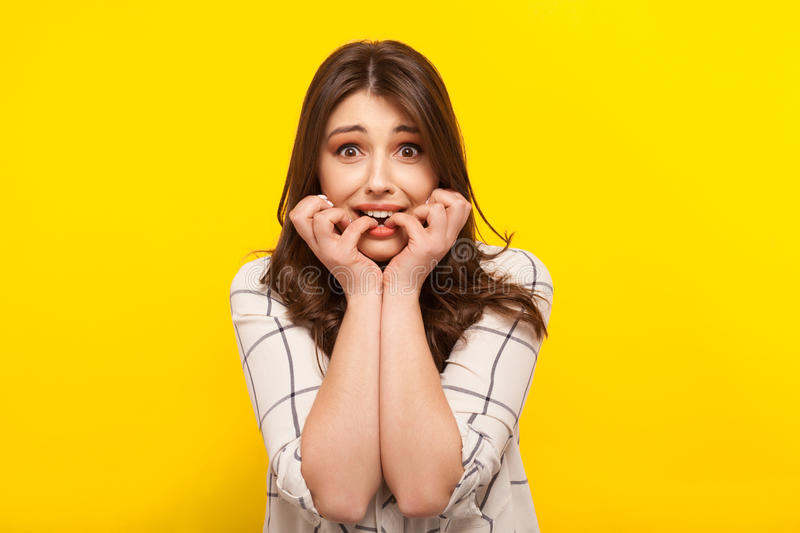 Scared girl posing on yellow royalty free stock photo