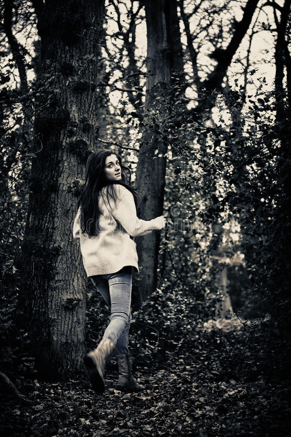 Scared girl running. Teenage girl running scared away from camera in woods stock photos